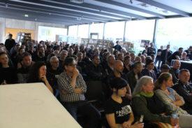 Raum ist gut gefüllt, Publikum wirk skeptisch